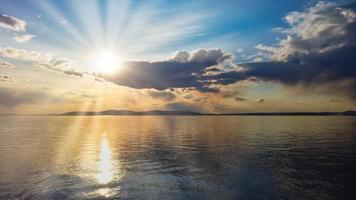 paesaggio marino con cielo nuvoloso colorato su un corpo d'acqua foto