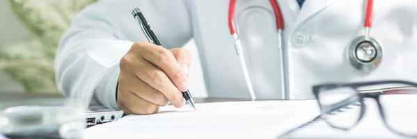 primo piano mano del medico che scrive i sintomi della malattia dopo la ricerca e il trattamento del paziente foto