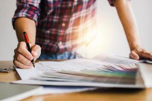 designer creativo controlla e scrive su carta sul tavolo foto