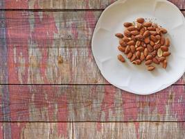 mandorle sulla zolla bianca sul fondo della tavola in legno foto