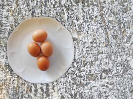 uova marroni su un piatto bianco su uno sfondo di roccia o muro di pietra foto