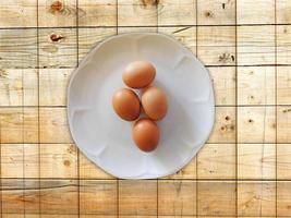 uova marroni su un piatto bianco su uno sfondo di tavolo in legno foto
