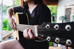 primo piano di una donna che suona una chitarra foto