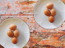 uova marroni su due piatti bianchi su uno sfondo di tavolo in legno foto
