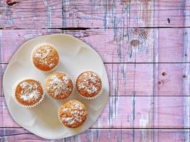 muffin su un piatto bianco su uno sfondo di tavolo in legno foto
