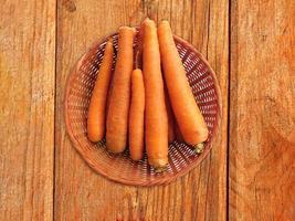 carote in un cesto di vimini su uno sfondo di tavolo in legno foto