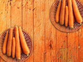 carote in due cesti di vimini su uno sfondo di tavolo in legno foto