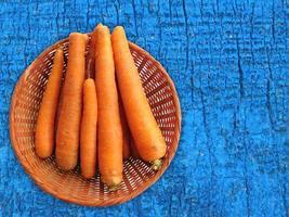 carote in un cesto di vimini su uno sfondo di tavolo in legno blu foto