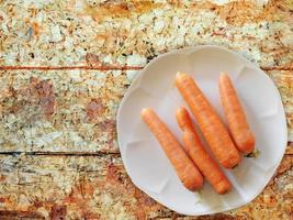 carote su un piatto bianco su uno sfondo di tavolo in legno foto