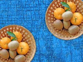 kiwi e arance in due cesti di vimini su uno sfondo di tavolo in legno foto