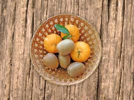kiwi e arance in un cesto di vimini su uno sfondo di tavolo in legno foto
