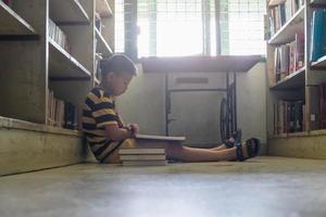 ragazzo che legge in una biblioteca foto