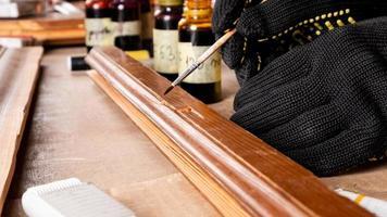 una mano che elimina i difetti di scheggiatura con un pennello, restauro della porta in legno foto