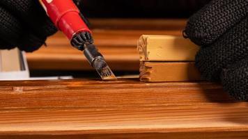una mano che elimina i difetti del truciolo, restauro della porta in legno foto