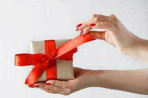 regalo con un nastro rosso in mano su uno sfondo bianco foto