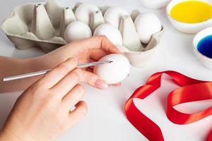 giovane donna dipinge uova bianche per Pasqua. foto