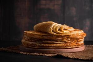 una pila di frittelle sottili su uno sfondo di legno scuro. un piatto tradizionale di crepes per la festa maslenitsa.