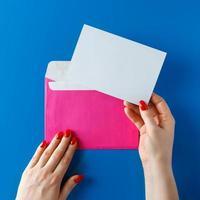 busta rosa con un biglietto vuoto in mano su sfondo blu. foto