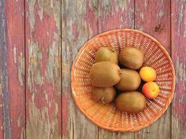kiwi e albicocche in un cesto di vimini su uno sfondo di tavolo in legno foto