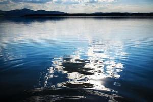 riflesso del cielo su un lago in tempesta foto