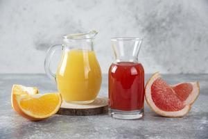 due bicchieri di pompelmo e succo d'arancia su uno sfondo di pietra foto