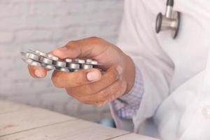 primo piano del medico che tiene confezioni blister foto