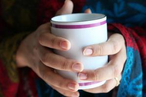 stretta di mano della donna che tiene la tazza di caffè foto