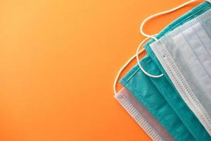 Close up di maschere chirurgiche blu su sfondo arancione foto
