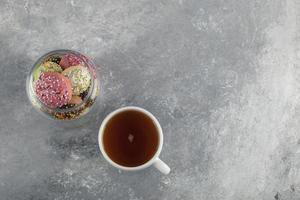 un barattolo di vetro pieno di piccole ciambelle colorate con una tazza di tè caldo foto