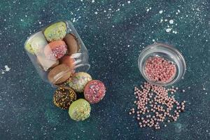 un barattolo di vetro pieno di piccole ciambelle colorate foto