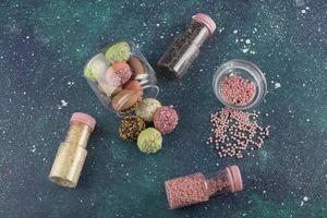 un barattolo di vetro pieno di piccole ciambelle colorate e bottiglie di confettini foto