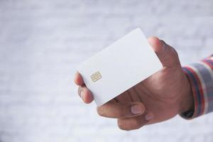mano che tiene la carta di credito bianca foto