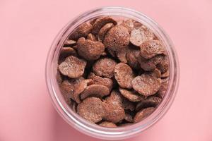 vista dall'alto di fiocchi di mais al cioccolato in una ciotola su sfondo rosa foto