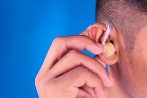 concetto di apparecchio acustico su sfondo blu foto