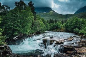 fiume in Norvegia che scorre lungo il fianco di una montagna foto