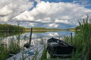 barca a remi legata a un molo in un lago vetroso in Svezia foto