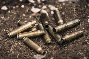 pila di proiettili di munizioni usati sul terreno foto