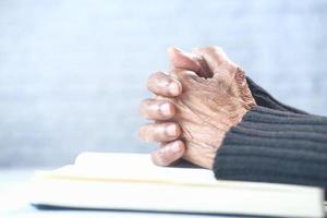 mani della donna che pregano su un libro foto