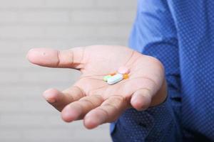 Close up di una mano di uomo che tiene le pillole foto