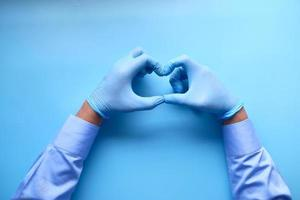 mani del medico che formano una forma di cuore su sfondo blu foto