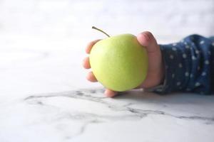 mano del bambino che tiene mela verde su sfondo neutro foto