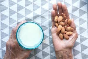 mano che tiene le mandorle e un bicchiere di latte foto