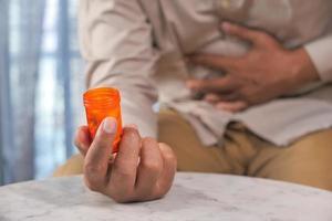 uomo con mal di stomaco che tiene una bottiglia di pillola arancione foto