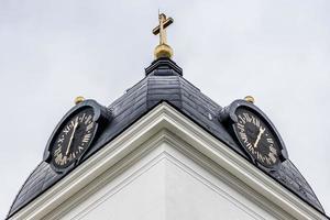 basso angolo di visione della torre dell'orologio da una chiesa bianca in svezia foto