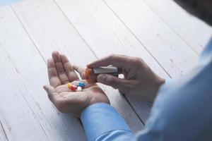 uomo che prende alcune pillole foto