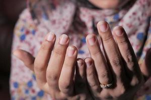 mani della donna che pregano su sfondo scuro foto