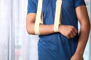 uomo in camicia blu che indossa l'imbracatura del braccio foto