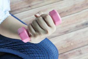 giovane donna che si esercita con i pesi con manubri foto