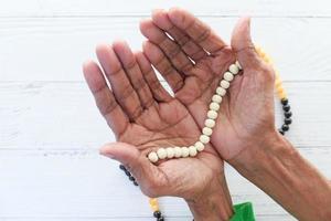 mani della donna che tengono i grani di preghiera foto