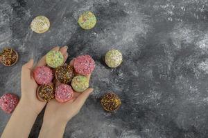 mani che tengono piccole ciambelle dolci colorate con spruzza foto